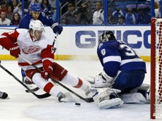 TAMPA, FL - DECEMBER 12:  Ben Bishop #30 of the Tampa Bay Lightning makes a save on Justin Abdelkader #8 of the Detroit Red Wings as he's defended by Sami Salo #6 at the Tampa Bay Times Forum on December 12, 2013 in Tampa, Florida. (Photo by Mike Carlson/Getty Images)