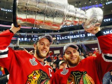 CHICAGO, IL - JUNE 15:  Jonathan Toews #19 and Patrick Kane #88 of the Chicago Blackhawks celebrate by hoisting the Stanley Cup after defeating the Tampa Bay Lightning by a score of 2-0 in Game Six to win the 2015 NHL Stanley Cup Final at the United Center on June 15, 2015 in Chicago, Illinois.  (Photo by Bruce Bennett/Getty Images)