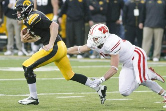 IOWA CITY, IA - NOVEMBER 22: Quarterback Jake Rudock #15 of the Iowa Hawkeyes is tripped up on a keeper by linebacker Vince Biegel #47 of the Wisconsin Badgers, in the first quarter on November 22, 2014 at Kinnick Stadium, in Iowa City, Iowa. (Photo by Matthew Holst/Getty Images)