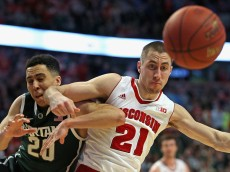 CHICAGO, IL - MARCH 15: Josh Gasser #21 of the Wisconsin Badgers throws an elbow into Travis Trice #20 of the Michigan State Spartans as they chase  loose ball during the Championship game of the 2015 Big Ten Men's Basketball Tournament at the United Center on March 15, 2015 in Chicago, Illinois. Wisconsin defeated Michigan State 80-69 in overtime. (Photo by Jonathan Daniel/Getty Images)