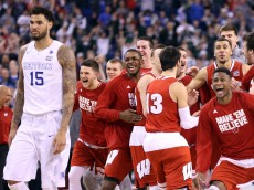 INDIANAPOLIS, IN - APRIL 04: The Wisconsin Badgers celebrate after defeating the Kentucky Wildcats as Willie Cauley-Stein #15 looks on during the NCAA Men's Final Four Semifinal at Lucas Oil Stadium on April 4, 2015 in Indianapolis, Indiana.  Wisconsin defeated Kentucky  71-64. (Photo by Andy Lyons/Getty Images)