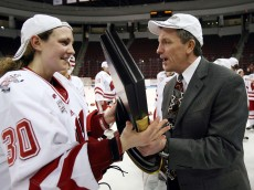 BOSTON - MARCH 22:  Jessie Vetter #30 of the Wisconsin Badgers hands off the championship trophy to head coach Mark Johnson after they defeated the Mercyhurst Lakers on March 22, 2009 during the NCAA Women's Frozen Four Championship game at Agganis Arena in Boston, Massachusetts. The Wisconsin Badgers defeated the Mercyhurst Lakers 5-0.  (Photo by Elsa/Getty Images)