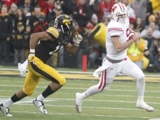 IOWA CITY, IA - NOVEMBER 22: Quarterback Tanner McEvoy #15 of the Wisconsin Badgers runs on a keeper in front of defensive back Greg Mabin #13 of the Iowa Hawkeyes, in the second quarter on November 22, 2014 at Kinnick Stadium, in Iowa City, Iowa. (Photo by Matthew Holst/Getty Images)
