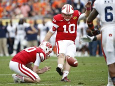 TAMPA, FL - JANUARY 1:  Place kicker Rafael Gaglianone #10 of the Wisconsin Badgers gets a hold from punter Drew Meyer #90 as he kicks what proved to be the game-winning 25 yard field goal in overtime during the Outback Bowl against the Auburn Tigers on January 1, 2015 at Raymond James Stadium in Tampa, Florida.  (Photo by Brian Blanco/Getty Images)