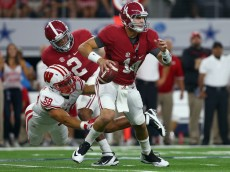 ARLINGTON, TX - SEPTEMBER 05:  Jake Coker #14 of the Alabama Crimson Tide scrambles with the ball under pressure from Joe Schobert #58 of the Wisconsin Badgers in the first quarter during The Advocare Classic at AT&T Stadium on September 5, 2015 in Arlington, Texas.  (Photo by Tom Pennington/Getty Images)