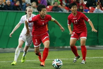 TORONTO, ON - AUGUST 16:  Choe Sol Gyong of Korea DPR gets past Rose Lavelle of the United States during the FIFA U-20 Women's World Cup Canada 2014 Quarter Final match between Korea DPR and the United States at the National Soccer Stadium on August 16, 2014 in Toronto, Ontario, Canada.  (Photo by Vaughn Ridley/Getty Images)