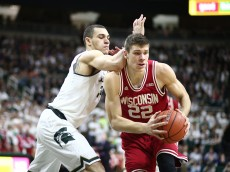 EAST LANSING, MI - FEBRUARY  18:  Ethan Happ #22 of the Wisconsin Badgers handles the ball under pressure from Gavin Schilling #34 of the Michigan State Spartans in the first half at the Breslin Center on February 18, 2016 in East Lansing, Michigan. (Photo by Rey Del Rio/Getty Images)