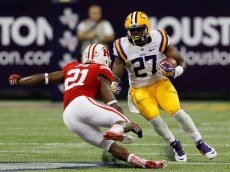 HOUSTON, TX - AUGUST 30:  Kenny Hilliard #27 of the LSU Tigers rushes past Peniel Jean #21 of the Wisconsin Badgers at NRG Stadium on August 30, 2014 in Houston, Texas.  (Photo by Bob Levey/Getty Images)