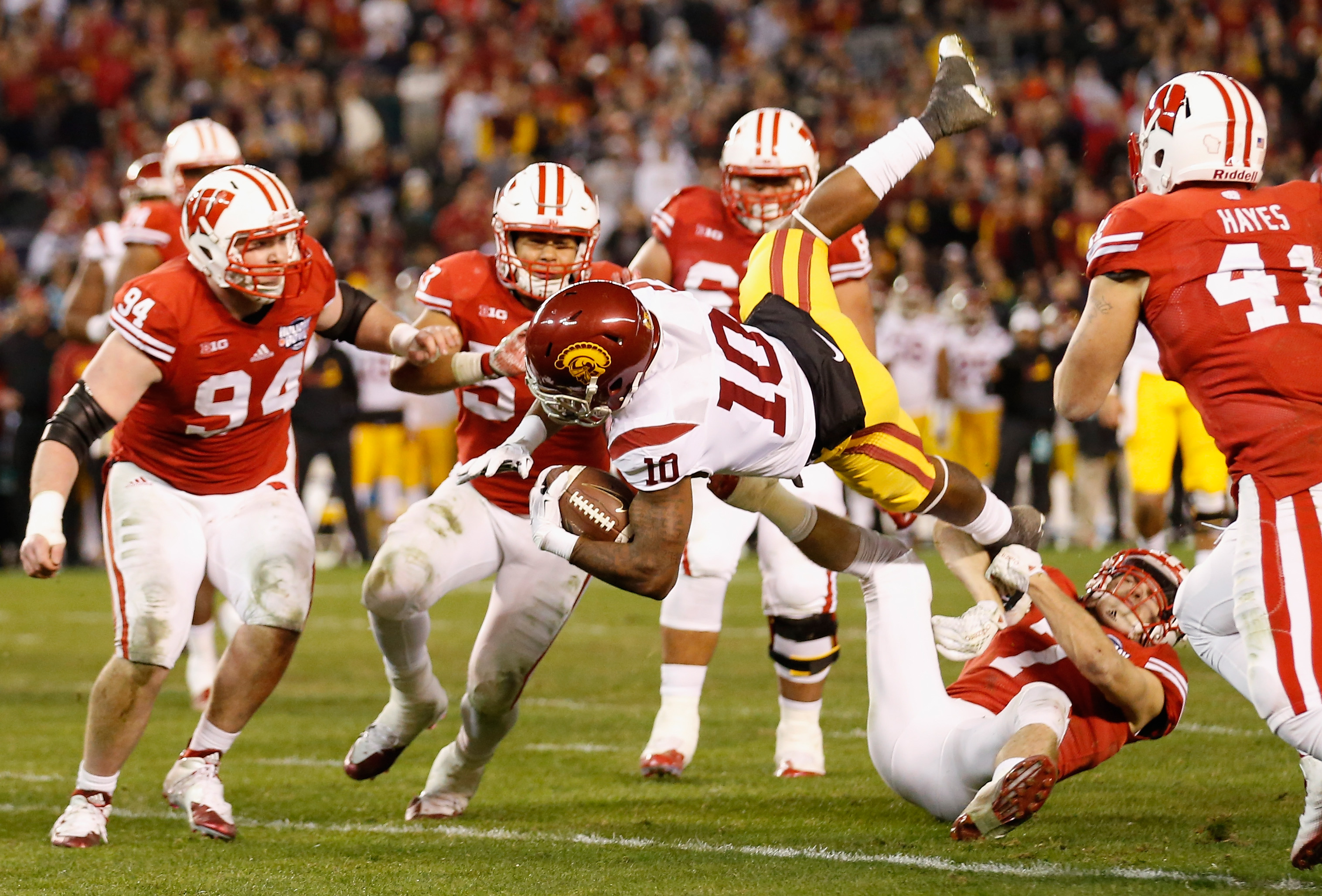 SAN DIEGO, CA - DECEMBER 30:  Jalen Greene #10 of the USC Trojans is upended while being tackled by Michael Caputo #7 of the Wisconsin Badgers and Conor Sheehy #94 of the Wisconsin Badgers during the second half of the National University Holiday Bowl at Qualcomm Stadium on December 30, 2015 in San Diego, California.  (Photo by Sean M. Haffey/Getty Images)