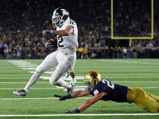 SOUTH BEND, IN - SEPTEMBER 17:  R.J. Shelton #12 of the Michigan State Spartans scores a touchdown in front of Drue Tranquill #23 of the Notre Dame Fighting Irish during the first half of a game at Notre Dame Stadium on September 17, 2016 in South Bend, Indiana.  (Photo by Stacy Revere/Getty Images)