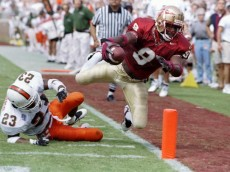 3 Oct 1997:  Flanker Peter Warrick of the Florida State Seminoles (right) makes a touchdown as cornerback Duane Starks of the Miami Hurricanes (left) misses the tackle during a game at Doak S. Campbell Stadium in Tallahassee, Florida.  Florida State won the game 47-0. Mandatory Credit: Andy Lyons  /Allsport
