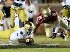 TALLAHASSEE, FL - OCTOBER 18:  Everett Golson #5 of the Notre Dame Fighting Irish dives with the ball as Jacob Pugh #16 of the Florida State Seminoles tries to make the stop during their game at Doak Campbell Stadium on October 18, 2014 in Tallahassee, Florida.  (Photo by Streeter Lecka/Getty Images)