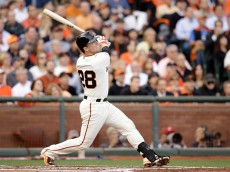 SAN FRANCISCO, CA - OCTOBER 15:  Buster Posey #28 of the San Francisco Giants hits a RBI sacrifice fly ball in the first inning against the St. Louis Cardinals during Game Four of the National League Championship Series at AT&T Park on October 15, 2014 in San Francisco, California.  (Photo by Ezra Shaw/Getty Images)
