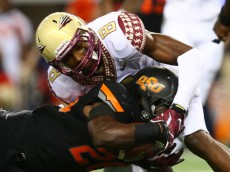 ARLINGTON, TX - AUGUST 30:  Desmond Roland #26 of the Oklahoma State Cowboys is tackled by Jalen Ramsey #8 of the Florida State Seminoles in the first half of the Advocare Cowboys Classic at AT&T Stadium on August 30, 2014 in Arlington, Texas.  (Photo by Ronald Martinez/Getty Images)