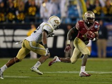 CHARLOTTE, NC - DECEMBER 06: Dalvin Cook #4 of the Florida State Seminoles runs the ball against Demond Smith #12 of the Georgia Tech Yellow Jackets in the 3rd quarter during the ACC Championship game on December 6, 2014 in Charlotte, North Carolina. (Photo by Mike Ehrmann/Getty Images)