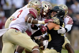 WINSTON SALEM, NC - OCTOBER 03:  Derwin James #3, Jacob Pugh #16 and Trey Marshall #20 of the Florida State Seminoles tackle Cam Serigne #85 of the Wake Forest Demon Deacons during their game at BB&T Field on October 3, 2015 in Winston Salem, North Carolina. Florida State won 24-16.  (Photo by Grant Halverson/Getty Images)