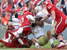 RALEIGH, NC - SEPTEMBER 27:  Jacoby Brissett #12 of the North Carolina State Wolfpack completes a pass under pressure from the Florida State Seminoles during their game at Carter-Finley Stadium on September 27, 2014 in Raleigh, North Carolina. Florida State won 56-41.  (Photo by Grant Halverson/Getty Images)