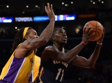 LOS ANGELES, CA - NOVEMBER 12:  Jrue Holiday #11 of the New Orleans Pelicans attempts a layup past Jordan Hill #27 of the Los Angeles Lakers during the first quarter at Staples Center on November 12, 2013 in Los Angeles, California.  NOTE TO USER: User expressly acknowledges and agrees that, by downloading and or using this Photograph, user is consenting to the terms and condition of the Getty Images License Agreement.  (Photo by Harry How/Getty Images)