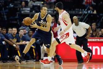 HOUSTON, TX - JANUARY 10:  Rudy Gobert #27 of the Utah Jazz looks to pass the basketball in front of Kostas Papanikolaou #16 of the Houston Rockets during their game at the Toyota Center on January 10, 2015 in Houston, Texas.  NOTE TO USER: User expressly acknowledges and agrees that, by downloading and/or using this photograph, user is consenting to the terms and conditions of the Getty Images License Agreement.  (Photo by Scott Halleran/Getty Images)