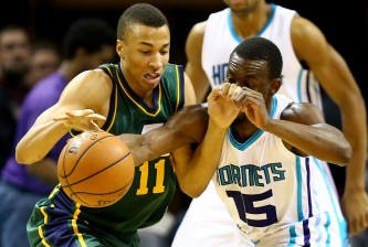 CHARLOTTE, NC - DECEMBER 20:  Dante Exum #11 of the Utah Jazz and Kemba Walker #15 of the Charlotte Hornets go after a loose ball during their game at Time Warner Cable Arena on December 20, 2014 in Charlotte, North Carolina.  NOTE TO USER: User expressly acknowledges and agrees that, by downloading and or using this photograph, User is consenting to the terms and conditions of the Getty Images License Agreement.  (Photo by Streeter Lecka/Getty Images)