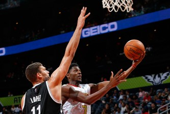 ATLANTA, GA - NOVEMBER 04:  Justin Holiday #7 of the Atlanta Hawks drives the basket against Brook Lopez #11 of the Brooklyn Nets at Philips Arena on November 4, 2015 in Atlanta, Georgia.  NOTE TO USER User expressly acknowledges and agrees that, by downloading and or using this photograph, user is consenting to the terms and conditions of the Getty Images License Agreement.  (Photo by Kevin C. Cox/Getty Images)