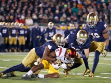 SOUTH BEND, IN - OCTOBER 17: KeiVarae Russell #6 and Joe Schmidt #38 of the Notre Dame Fighting Irish tackle JuJu Smith-Schuster #9 of the USC Trojans in the second half of the game at Notre Dame Stadium on October 17, 2015 in South Bend, Indiana. (Photo by Joe Robbins/Getty Images)