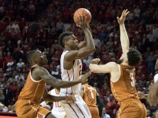 NORMAN, OK - FEBRUARY  8: Kendal Yancy #5 of the Texas Longhorns and Javan Felix #3 of the Texas Longhorns try to stop Buddy Hield #24 of the Oklahoma Sooners as he looks for a shot  during the second half of a NCAA college basketball game at the Lloyd Noble Center on February 8, 2016 in Norman, Oklahoma. Oklahoma won 63-60. (Photo by J Pat Carter/Getty Images)