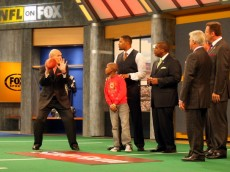 LOS ANGELES, CA - DECEMBER 12:  (L-R) FOX NFL Sunday host Terry Bradshaw demonstrates a move to St. Jude Children's Research Hospital patient Markell, analyst Michael Strahan, host Curt Menefee, analysts Jimmy Johnson and Howie Long and former NFL referee Mike Pereira during FOX NFL Sunday on December 12, 2010 in Los Angeles, United States.  (Photo by Victor Decolongon/Getty Images for St. Jude Children's Research Hospital)