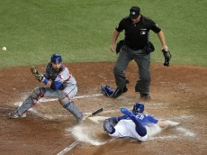 TORONTO, ON - OCTOBER 9: Josh Donaldson #20 of the Toronto Blue Jays slides safely into home plate past Jonathan Lucroy #25 of the Texas Rangers in the tenth inning for the Toronto Blue Jays to defeat the Texas Rangers 7-6 for game three of the American League Division Series at Rogers Centre on October 9, 2016 in Toronto, Canada. (Photo by Tom Szczerbowski/Getty Images)