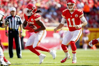 KANSAS CITY, MO - OCTOBER 11:  Jamaal Charles (25) of the Kansas City Chiefs runs the ball as Alex Smith (11) of the Kansas City Chiefs watches at Arrowhead Stadium during the game on October 11, 2015 in Kansas City, Missouri. (Photo by Jamie Squire/Getty Images)