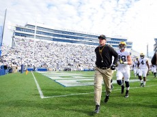 STATE COLLEGE, PA - NOVEMBER 21:  Jim Harbaugh head coach of the Michigan Wolverines runs onto the field prior to the game against the Penn State Nittany Lions at Beaver Stadium on November 21, 2015 in State College, Pennsylvania.  (Photo by Evan Habeeb/Getty Images)