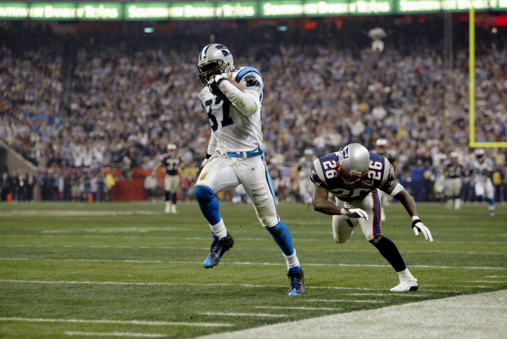 HOUSTON - FEBRUARY 1:  Wide receiver Muhsin Muhammad #87 of the Carolina Panthers evades cornerback Eugene Wilson #26 of the New England Patriots during Super Bowl XXXVIII at Reliant Stadium on February 1, 2004 in Houston, Texas.  The Patriots defeated the Panthers 32-29.  (Photo by Brian Bahr/Getty Images)