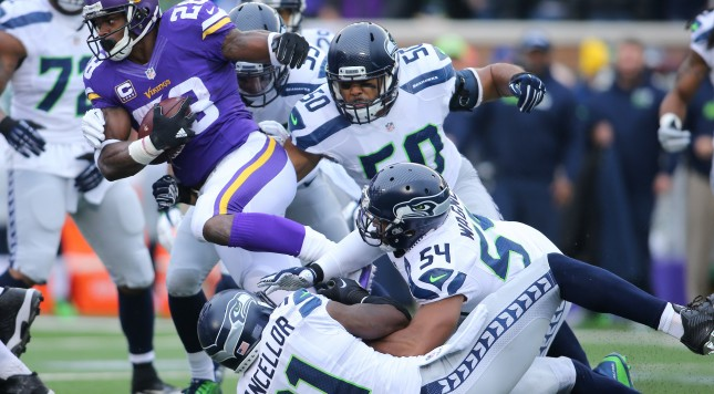 MINNEAPOLIS, MN - DECEMBER 6:  Adrian Peterson #28 of the Minnesota Vikings gets tackled by Kam Chancellor #31 of the Seattle Seahawks in the first quarter on December 6, 2015 at TCF Bank Stadium in Minneapolis, Minnesota. (Photo by Adam Bettcher/Getty Images)