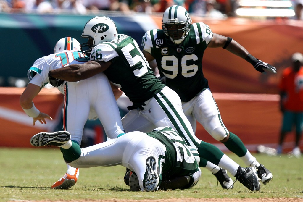 MIAMI - SEPTEMBER 07:  Shaun Ellis #92 (bottom) of the New York Jets sacks Chad Pennington #10 of the Miami Dolphins with pressure from teammates Vernon Gholston #56 and David Bowens #96 of the Jets at Dolphin Stadium on September 7, 2008 in Miami, Florida. The Jets won 20-14.  (Photo by Doug Benc/Getty Images)