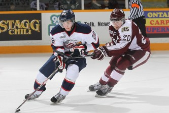 PETERBOROUGH, ON - FEBRUARY 20:  Jesse Graham #22 of the Saginaw Spirit is checked closely by Nick Ritchie #20 of the Peterborough Petes during an OHL game at the Memorial Centre on February 20, 2014 in Peterborough, Ontario, Canada. The Petes defeated the Spirit 5-2. (Photo by Claus Andersen/Getty Images)