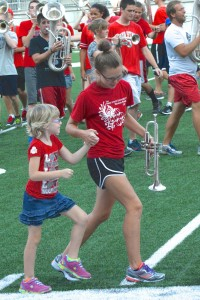 A TBDBITL member helps one of the kids from Nellie's Catwalk to march Script Ohio.
