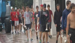 TBDBITL members walk back from a practice in the rain to meet with President Drake.