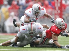 COLUMBUS, OH - APRIL 19:  Running back Daniel Herron #1 (R) of the Ohio State University Buckeyes is tackled by defenders Marcus Freeman #1 (L) and Etienne Sabino #6 during the second quarter of their Spring Game on April 19, 2008 at Ohio Stadium in Columbus, Ohio.  (Photo by Matt Sullivan/Getty Images)