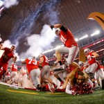 ARLINGTON, TX - JANUARY 12:  A Ohio State Buckeyes cheerleader falls as the Buckeyes run out to the field before the College Football Playoff National Championship Game at AT&T Stadium on January 12, 2015 in Arlington, Texas.  (Photo by Tom Pennington/Getty Images)