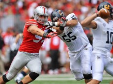 COLUMBUS, OH - SEPTEMBER 13:  Joey Bosa #97 of the Ohio State Buckeyes fights off a block from Reno Reda #55 of the Kent State Golden Flashes to pressure quarterback Colin Reardon #10 of the Kent State Golden Flashes in the second quarter at Ohio Stadium on September 13, 2014 in Columbus, Ohio.  (Photo by Jamie Sabau/Getty Images)
