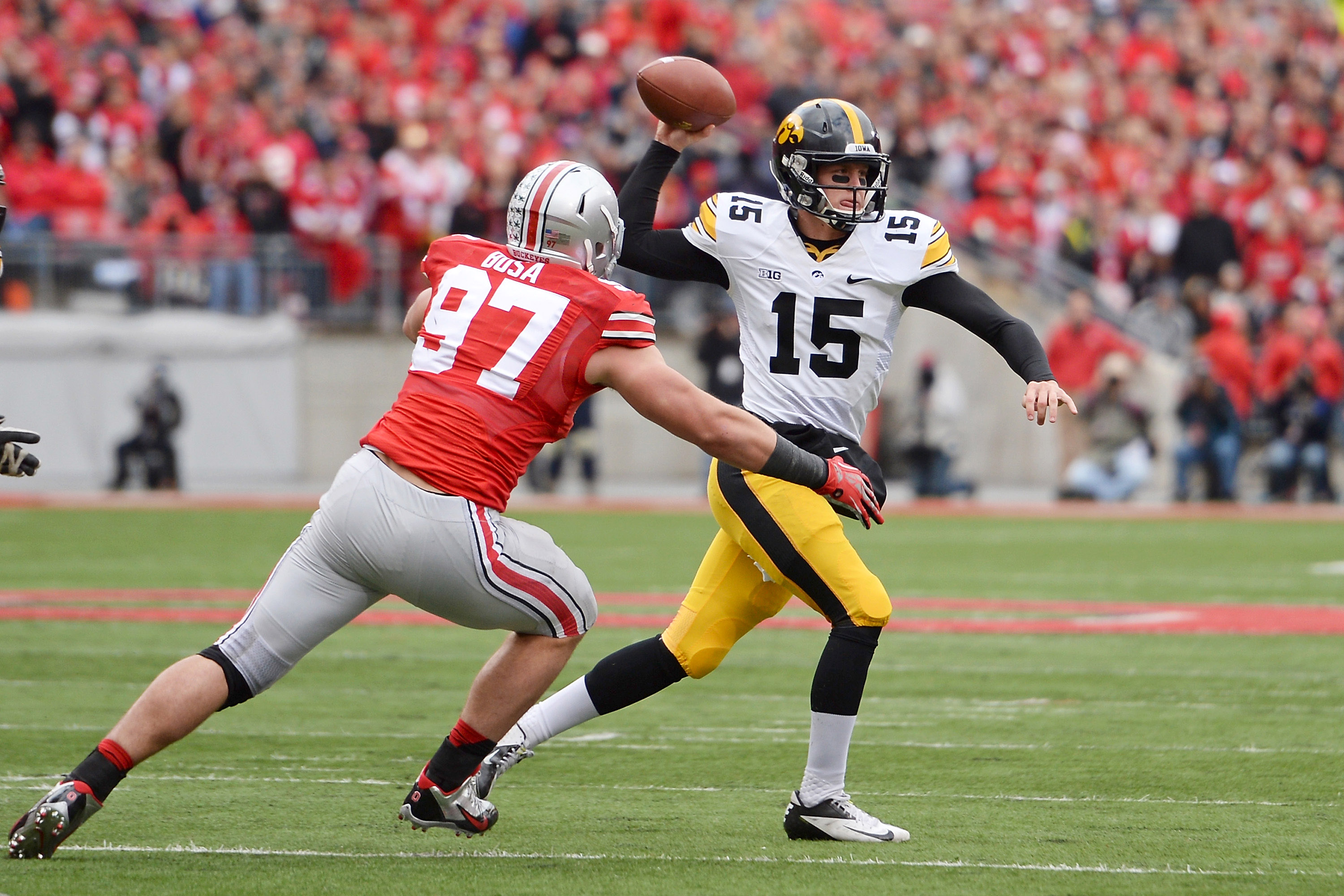 COLUMBUS, OH - OCTOBER 19:  Quarterback Jake Rudock #15 of the Iowa Hawkeyes passes in the second quarter as Joey Bosa #97 of the Ohio State Buckeyes applies pressure at Ohio Stadium on October 19, 2013 in Columbus, Ohio.  Ohio State defeated Iowa 34-24.   (Photo by Jamie Sabau/Getty Images)