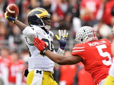 COLUMBUS, OH - NOVEMBER 29:  Quarterback Devin Gardner #98 of the Michigan Wolverines tosses a 12-yard touchdown pass as he is rushed by Raekwon McMillan #5 of the Ohio State Buckeyes in the first quarter at Ohio Stadium on November 29, 2014 in Columbus, Ohio.  (Photo by Jamie Sabau/Getty Images)