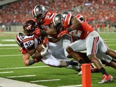 COLUMBUS, OH - SEPTEMBER 6:  Joshua Perry #37 and Doran Grant #12 of the Ohio State Buckeyes gang up to stop Marshawn Williams #42 of the Virginia Tech Hokies short of the goal line in the first quarter at Ohio Stadium on September 6, 2014 in Columbus, Ohio.  (Photo by Jamie Sabau/Getty Images)