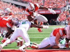 COLUMBUS, OH - SEPTEMBER 12:  Ezekiel Elliott #15 of the Ohio State Buckeyes scores on a 1-yard touchdown run past Jerrol Garcia-Williams #2 of the Hawaii Rainbow Warriors in the first quarter at Ohio Stadium on September 12, 2015 in Columbus, Ohio.  (Photo by Jamie Sabau/Getty Images)