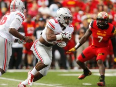 COLLEGE PARK, MD - OCTOBER 04:  Running back Ezekiel Elliott #15 (C) of the Ohio State Buckeyes takes a handoff from quarterback J.T. Barrett #16 (L) to run against the Maryland Terrapins during Ohio State's 52-24 win at Byrd Stadium on October 4, 2014 in College Park, Maryland.  (Photo by Jonathan Ernst/Getty Images)