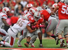 COLUMBUS, OH - OCTOBER 18:  Ezekiel Elliott #15 of the Ohio State Buckeyes is wrapped up by Kevin Snyder #45 of the Rutgers Scarlet Knights in the first quarter on October 18, 2014 at Ohio Stadium in Columbus, Ohio.  (Photo by Jamie Sabau/Getty Images)