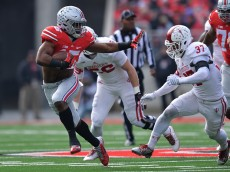 COLUMBUS, OH - NOVEMBER 22:  Ezekiel Elliott #15 of the Ohio State Buckeyes uses the stiff arm on Mark Murphy #37 of the Indiana Hoosiers during a first quarter run at Ohio Stadium on November 22, 2014 in Columbus, Ohio.  (Photo by Jamie Sabau/Getty Images)
