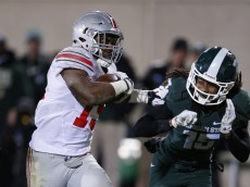 EAST LANSING, MI - NOVEMBER 8: Ezekiel Elliott #15 of the Ohio State Buckeyes rushes for a 17-yard touchdown ahead of Trae Waynes #15 of the Michigan State Spartans in the fourth quarter of the game at Spartan Stadium on November 8, 2014 in East Lansing, Michigan. (Photo by Joe Robbins/Getty Images)