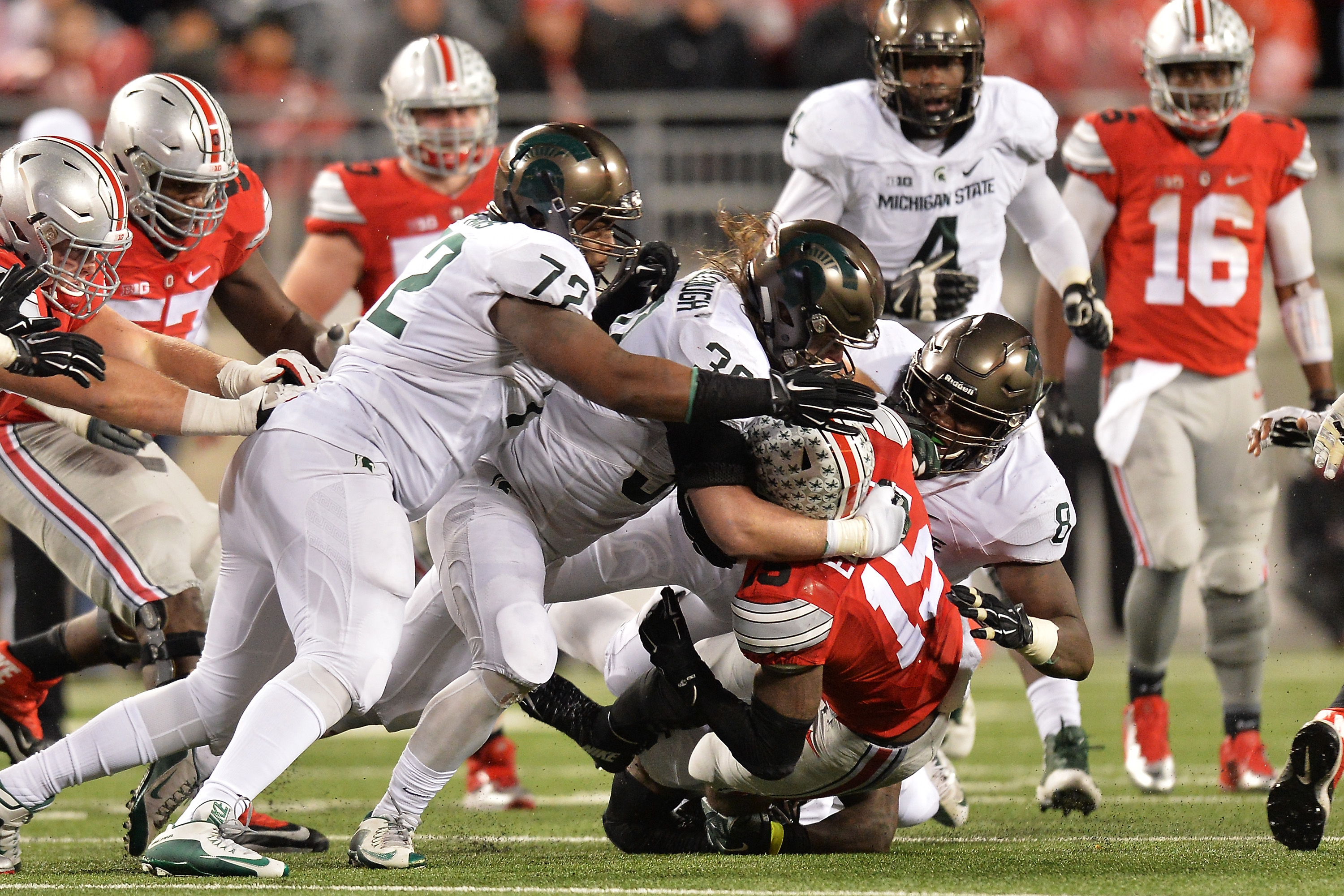 COLUMBUS, OH - NOVEMBER 21:  Ezekiel Elliott #15 of the Ohio State Buckeyes is gang tackled by Craig Evans #72 of the Michigan State Spartans, Riley Bullough #30 of the Michigan State Spartans and Lawrence Thomas #8 of the Michigan State Spartans in the third quarter at Ohio Stadium on November 21, 2015 in Columbus, Ohio. Michigan State defeated Ohio State 17-14.  (Photo by Jamie Sabau/Getty Images)