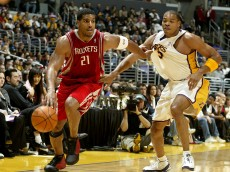 LOS ANGELES - DECEMBER 25:  Jim Jackson #21 of the Houston Rockets drives to the basket under pressure from Deavan George #3 of the Los Angeles Lakers on December 25, 2003 at the Staples Center in Los Angeles, California.  NOTE TO USER: User expressly acknowledges and agrees that, by downloading and/or using this Photograph, User is consenting to the terms and conditions of the Getty Images License Agreement.  (Photo by Lisa Blumenfeld/Getty Images)